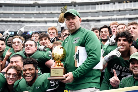 Ramapo head coach Drew Gibbs holds the trophy after his team defeats Summit in the North Group 3 Bowl Game on Saturday, Nov. 24, 2018, in East Rutherford.