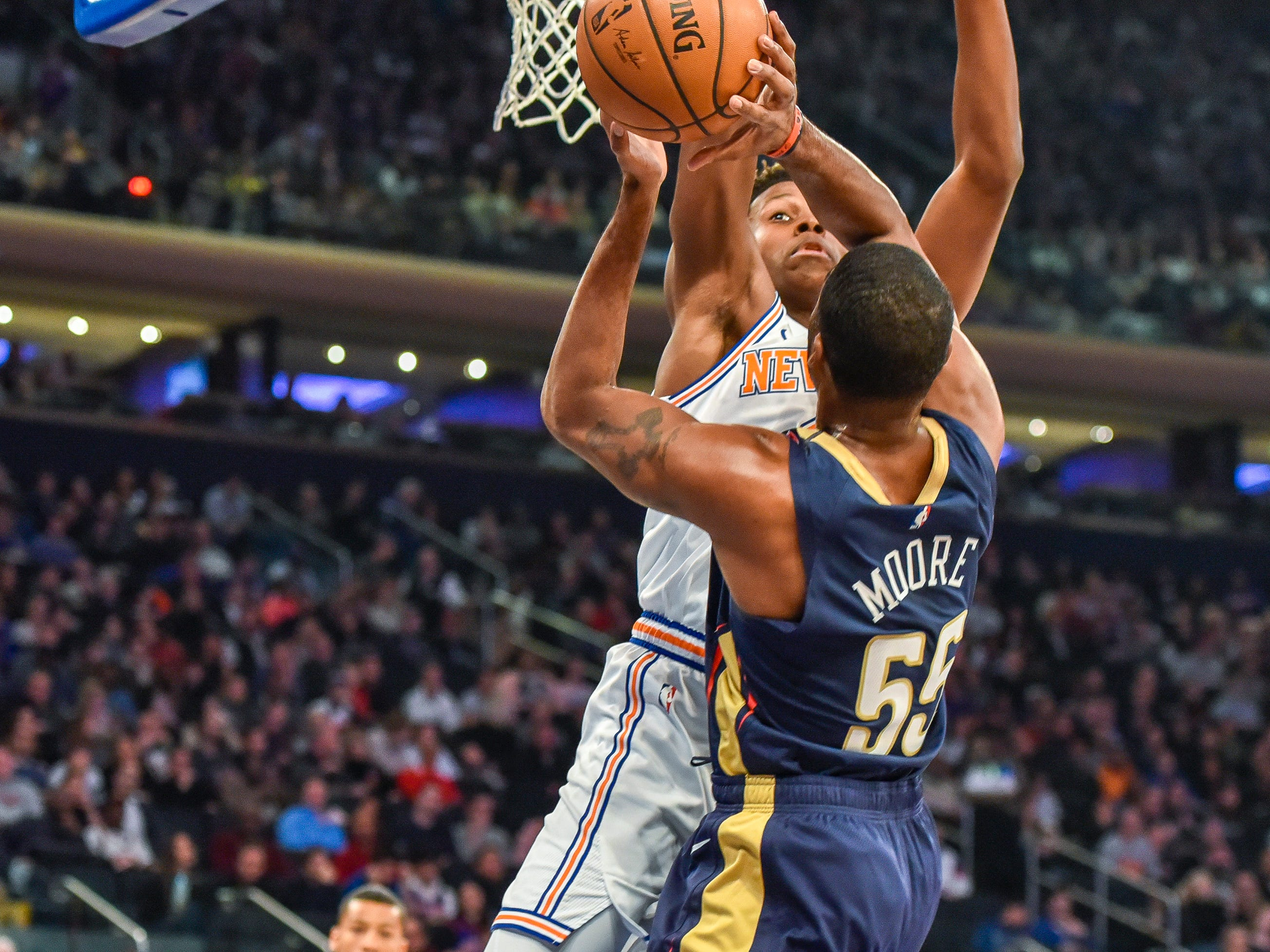 New York Knicks guard Frank Ntilikina (11) slaps away a shot-attempt of New Orleans Pelicans guard E'Twaun Moore (55) in the first quarter of an NBA basketball game, Friday, Nov. 23, 2018, in New York.
