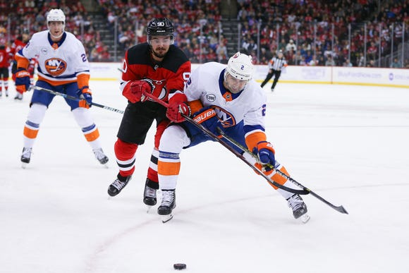 Nov 23, 2018; Newark, NJ, USA; New York Islanders defenseman Nick Leddy (2) battles for the puck against New Jersey Devils left wing Marcus Johansson (90) during the second period at Prudential Center.