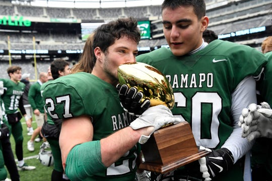 Ramapo's Max Baker (27) kisses the trophy after defeating Summit 42-22 in the North Group 3 Bowl Game on Saturday, Nov. 24, 2018, in East Rutherford.