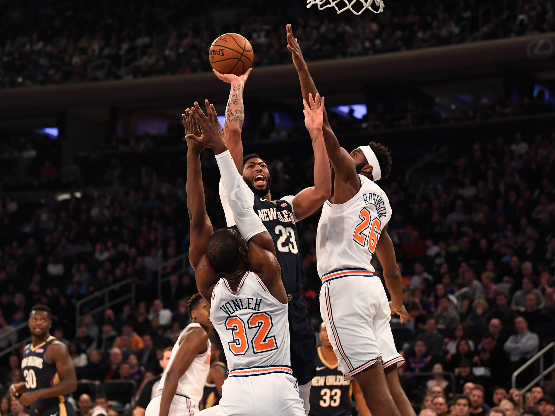Nov 23, 2018; New York, NY, USA; New Orleans Pelicans forward Anthony Davis (23) shoots the ball over New York Knicks forward Noah Vonleh (32) and center Mitchell Robinson (26) in the first quarter at Madison Square Garden.