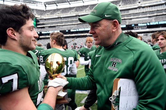 Ramapo head coach Drew Gibbs, right, hands the trophy to Max Baker after defeating Summit 42-22 in the North Group 3 Bowl Game on Saturday, Nov. 24, 2018, in East Rutherford.