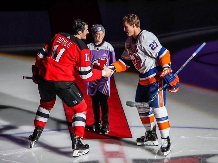Englewood's Bennett Burgida, an 11-year-old lymphoma survivor and lifelong Devils fan, center, with Devils forward Brian Boyle, left, and New York Islanders captain Anders Lee, right, for a ceremonial dropping of the puck before the Hockey Fights Cancer game at Prudential Center, Friday, Nov. 23, 2018.