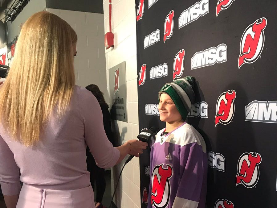 "Englewood's Bennett Burgida, 11, was the Devils' Hockey Fights Cancer honorary assistant coach during the game against the NY Islanders at Prudential Center on Friday, Nov. 23, 2018. He is being interviewed by Devils broadcast team member Erika Wachter. His message to the team: ""Play hard."""