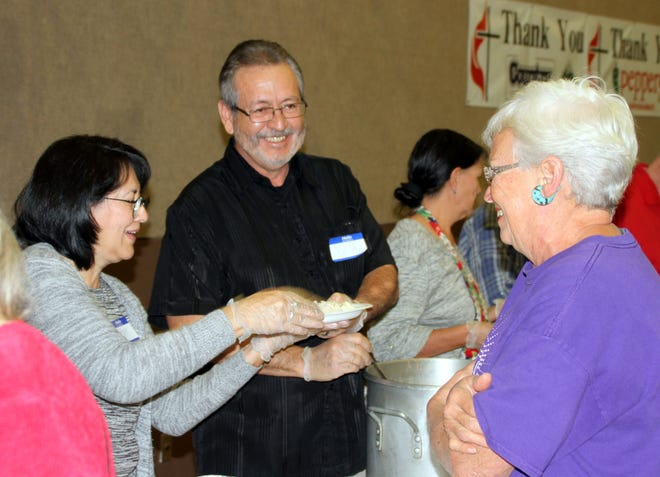 Pastor Cesar Chavez of River of Life Citi Church, and his wife, serve Thanksgiving dinner to Susan Schiffner, activities director for the Deming Senior Citizen's Center, on Thanksgiving Day at the First United Methodist Church in Deming, NM.