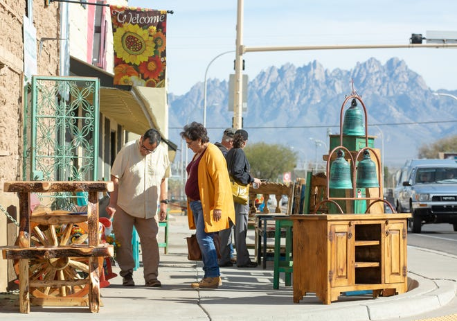 Richard Marquez of Phoenix, Arizona,  and Lupe Caballero, of Deming, New Mexico, look over items with other shoppers on Saturday in front of Coyote Traders Rustic Furniture on Saturday, Nov. 24, 2019, during Small Business Saturday. Coyote Traders store owners had mimosa on hand for their guests during the special day.