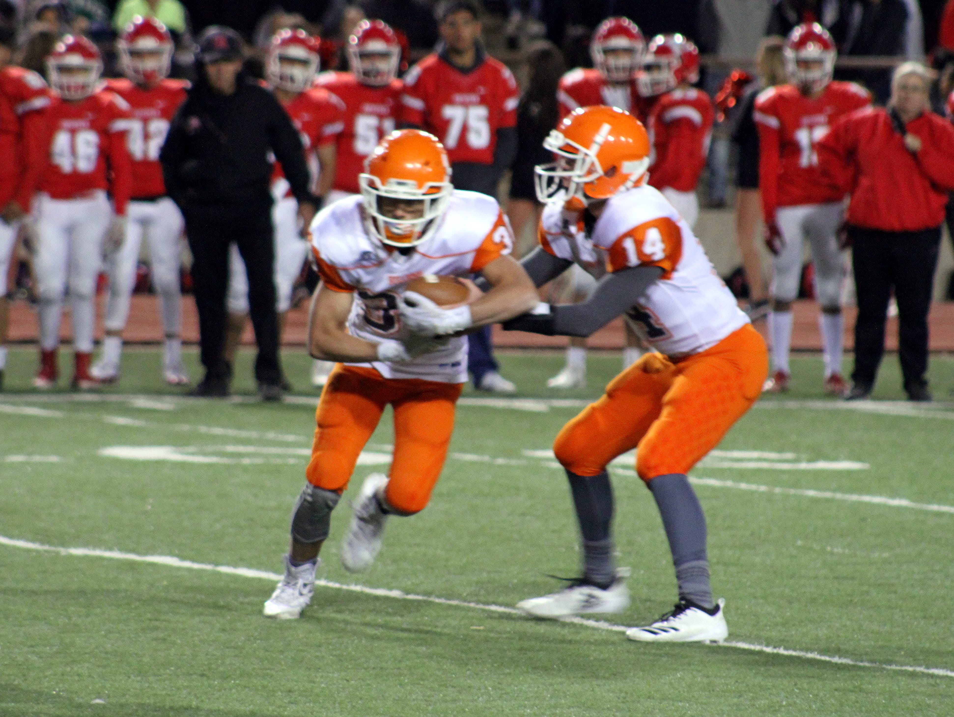 Trent Taylor (14) hands the ball off to Jagger Gonaghe (30) during Friday's Class 5A semifinal game. Both Artesia players were responsible for four touchdowns in the game.