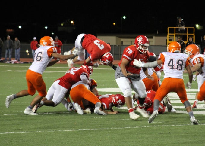 Roswell's Justin Carrasco (3) dives over the offensive line during Friday's Class 5A semifinal game. He finished the game with 183 yards of offense and two touchdowns.