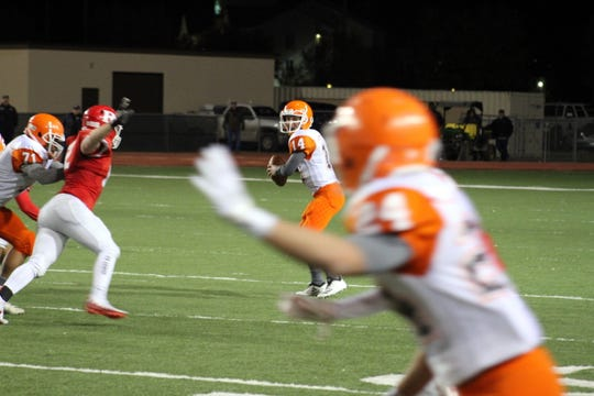 Trent Taylor (14) looks to pass to JR Bustamante (24) during Friday's Class 5A semifinal game. Taylor threw for 338 yards and four touchdowns. Bustamante had six catches for 49 yards and one touchdown.