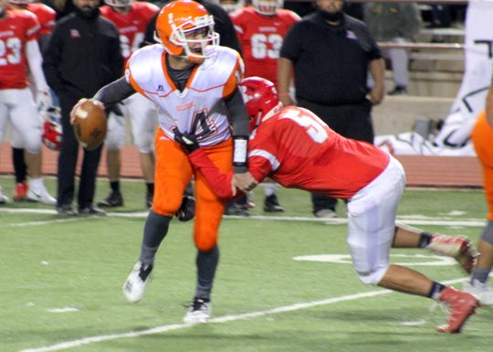 Artesia's Trent Taylor tries to escape a sack attempt by Roswell during Friday's Class 5A semifinal game.