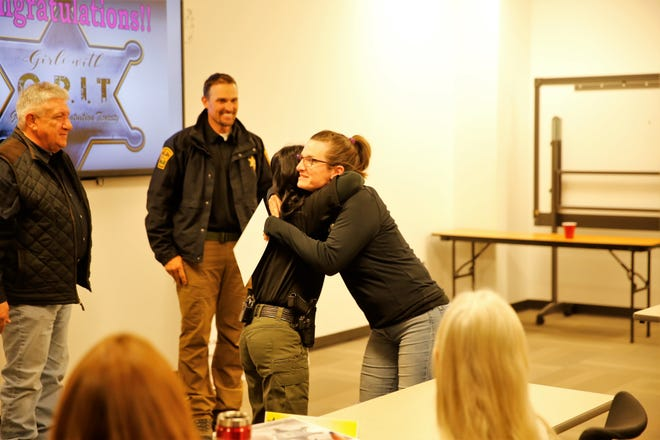Alicia Hunt hugs Sgt. Candice Mitchell, San Juan County criminal justice training authority director, during the last fall class of the San Juan County Sheriff's Office Girls with G.R.I.Tprogram on Nov. 13 in Aztec.