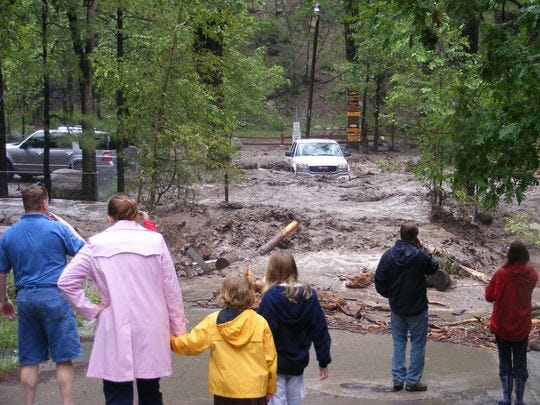 A family watches a white truck being swept away by the rising river.