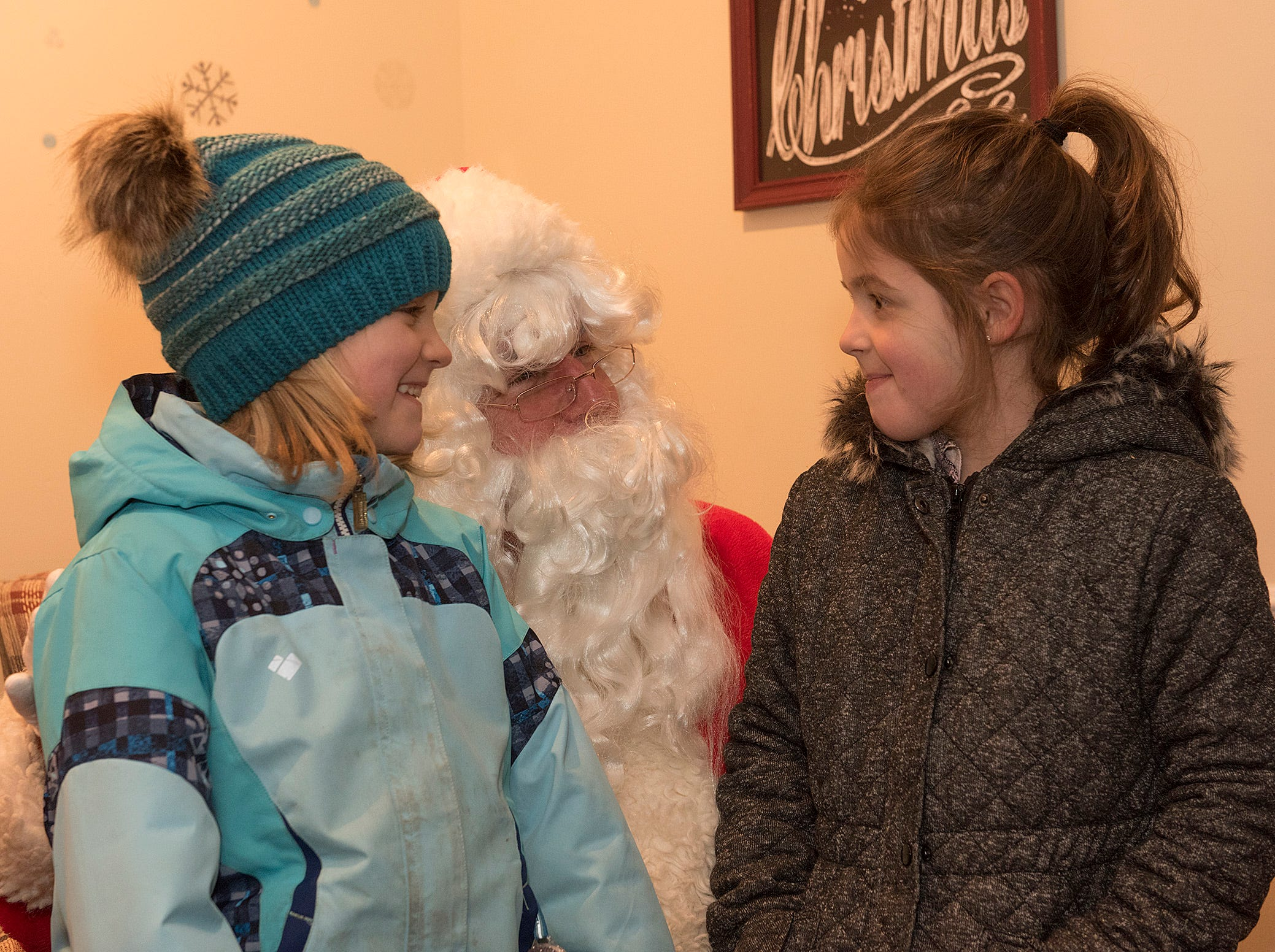 Caire Pryce and Brenna Hayward, both 6 years old, spend some time with Santa Claus.