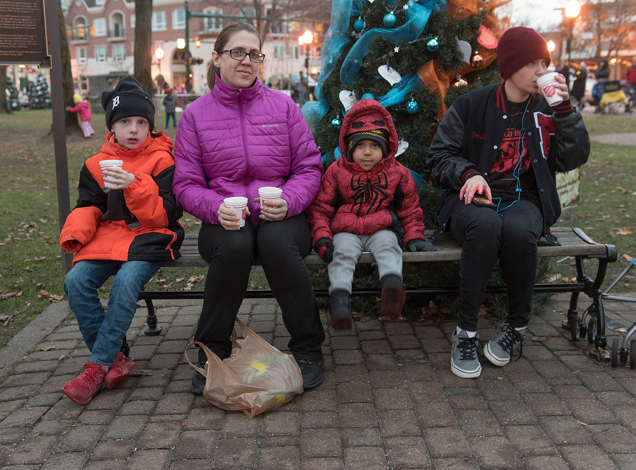 Sara Pouliet, with kids Jared, 6 years old, Joshua, 3 years old, and Jax, 17, enjoy hot chocolate before Santa's arrival. They are from Westland.
