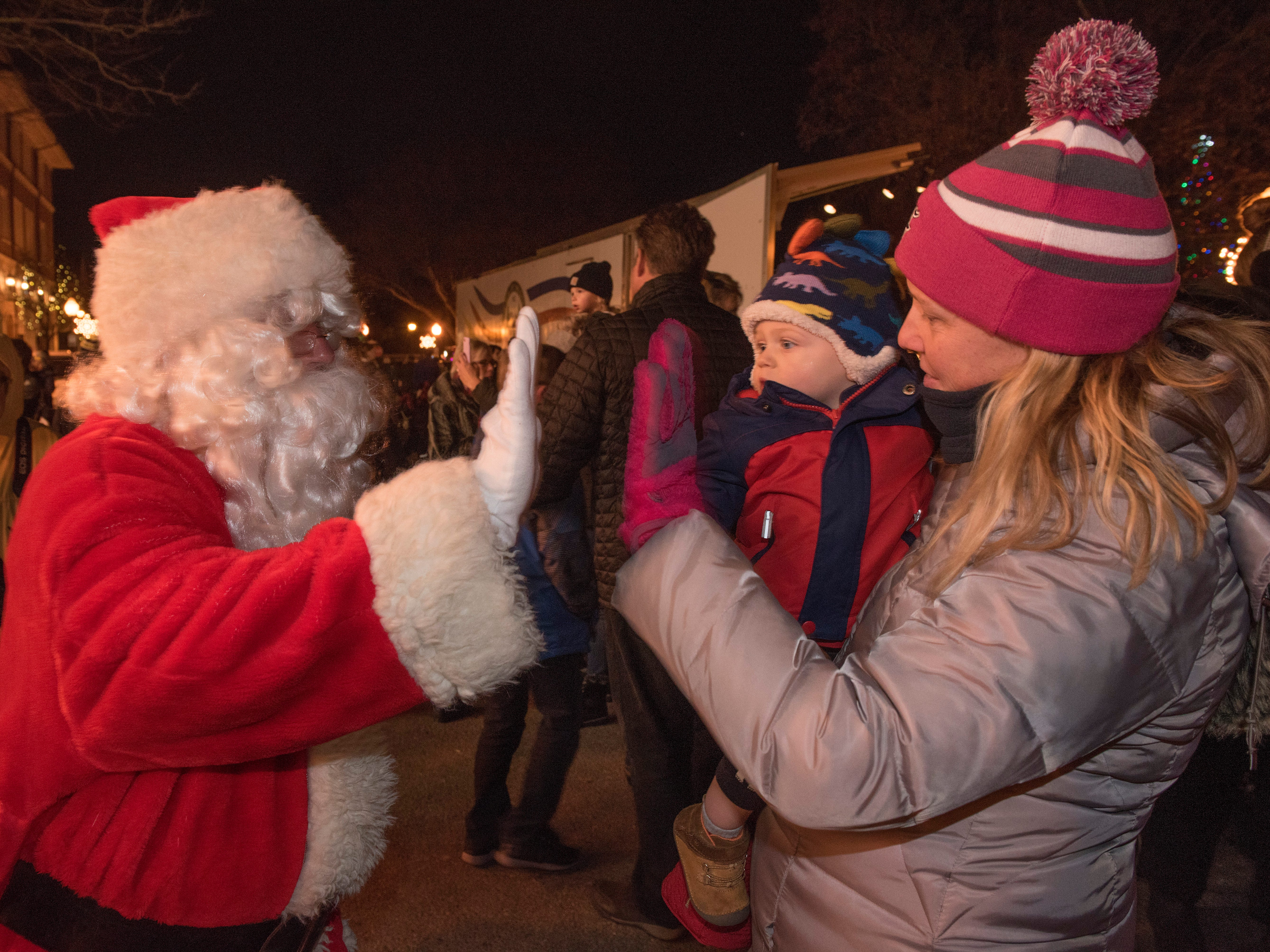 Santa Claus high fives Leslie McDougall, of Livonia, holding her nephew, 18 month old Carter Litfin.