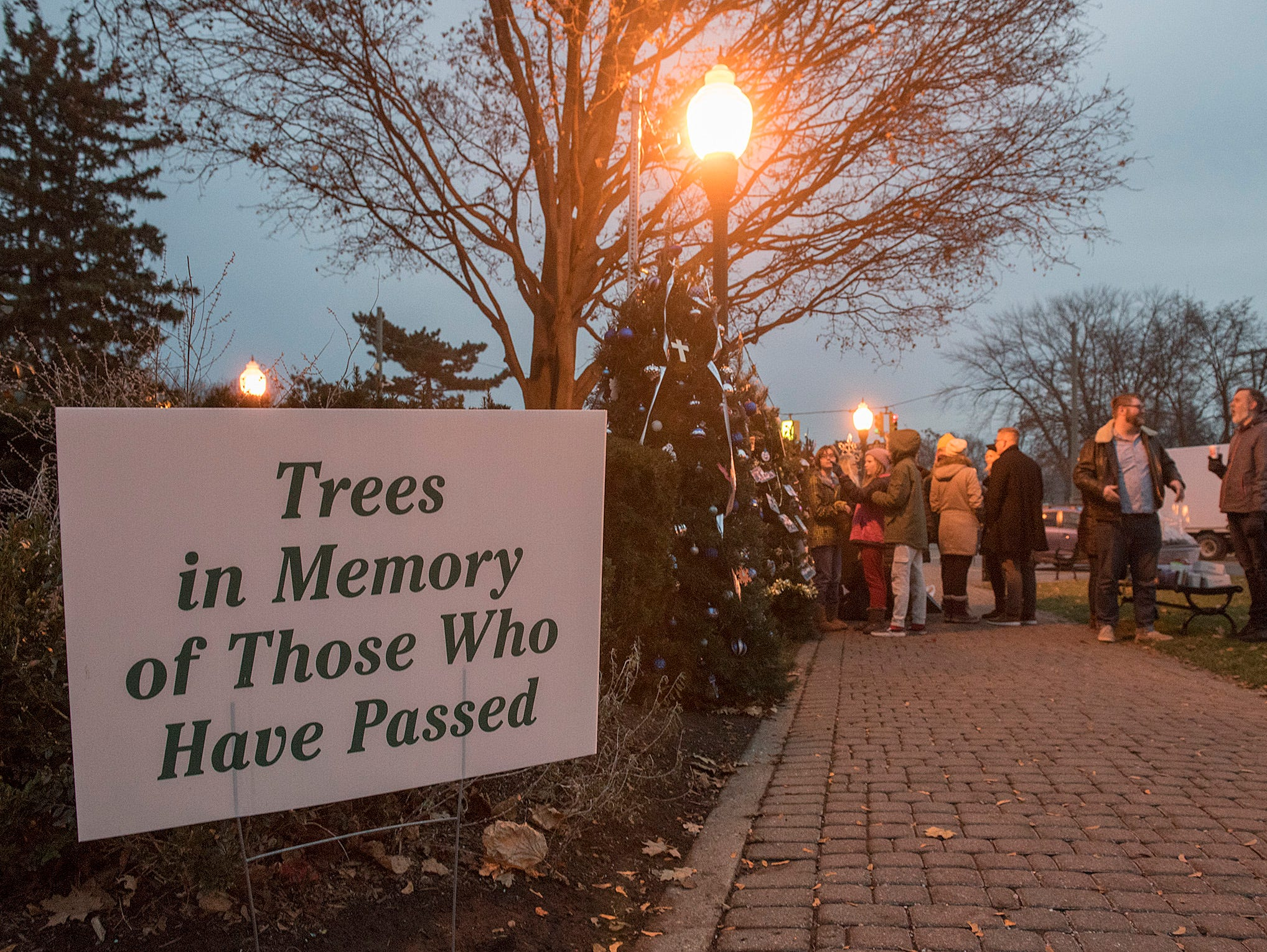 Families are decorating memorial trees to remember loved ones.