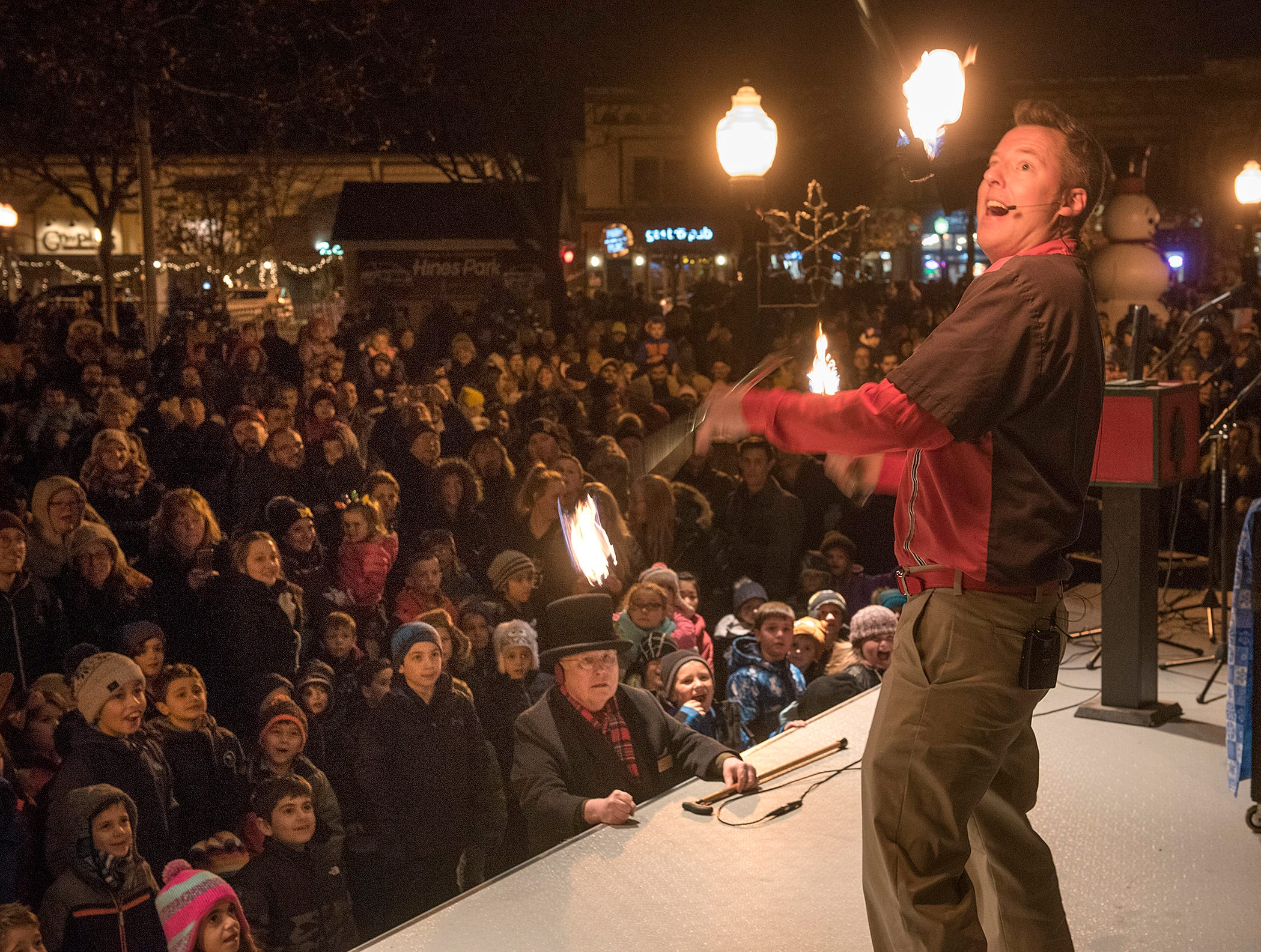 Magician Joel Tacey juggles fire batons, something that Santa Claus hardly ever does.