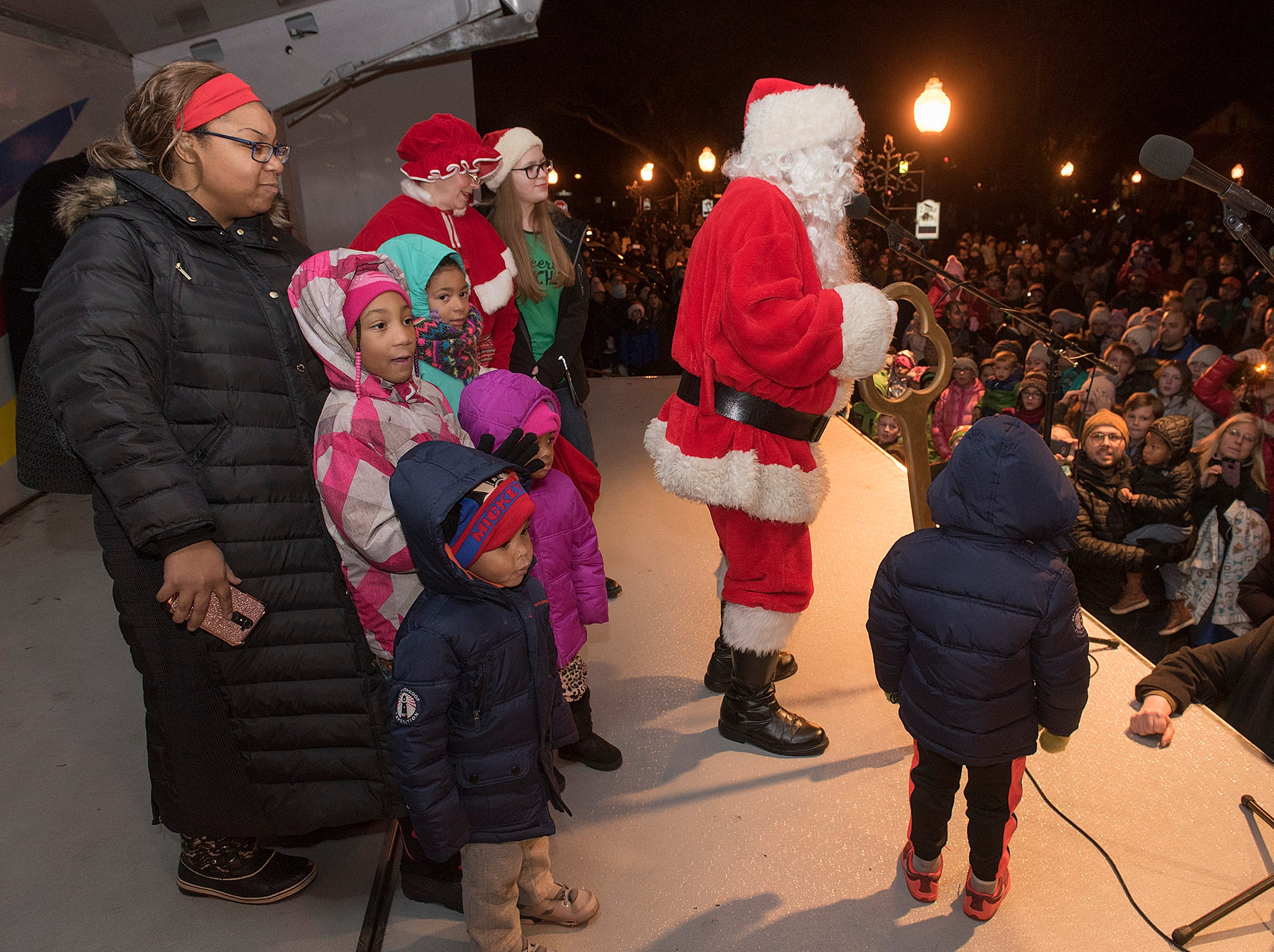Santa speaks to the crowd. Temeni Woods and kids Skylie, Taelyn, Olivia, Kayson, and Kaymon help out.