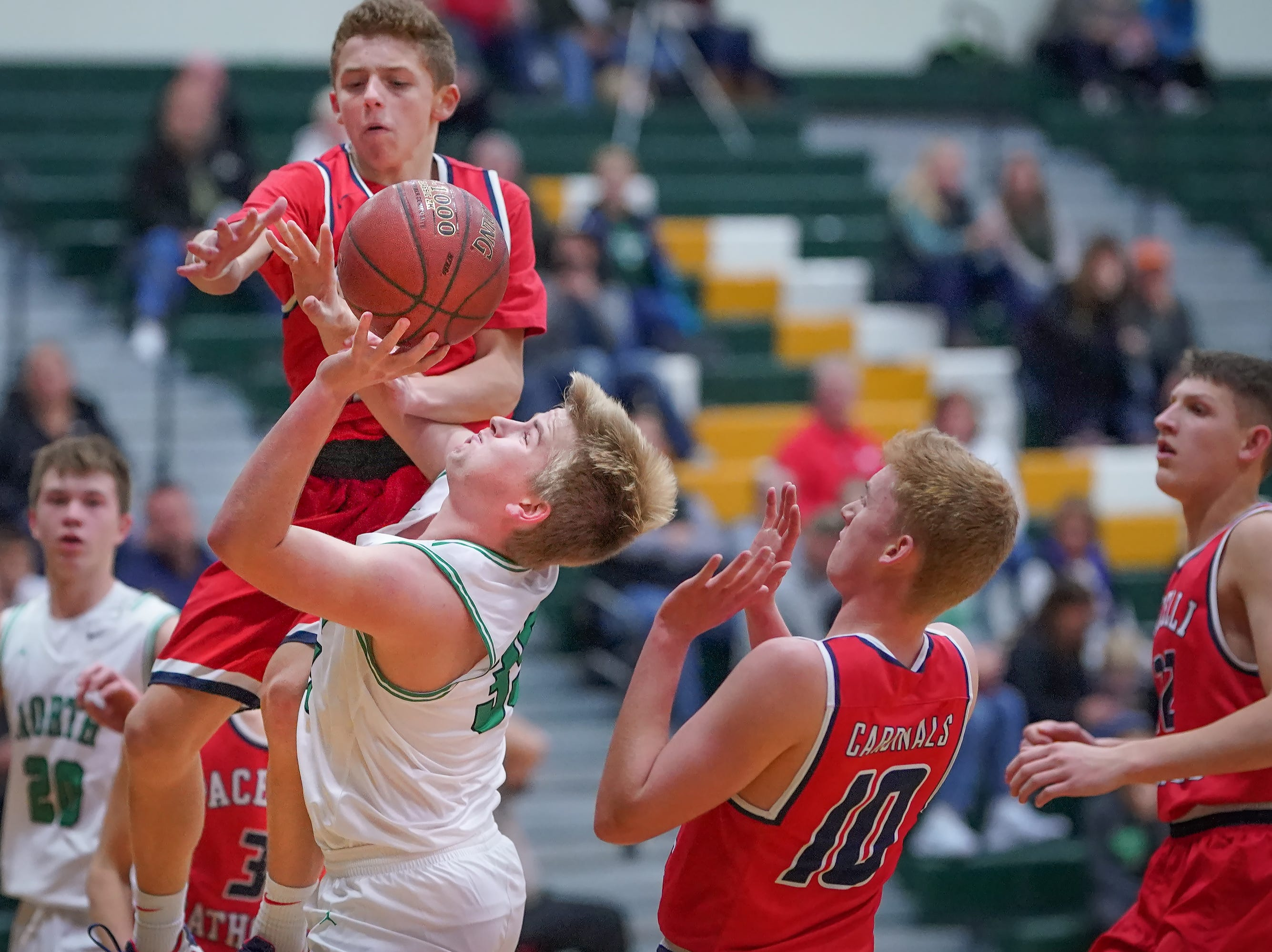 Scott Swanlund (35) of Oshkosh North gets fouled by Mason Schlagenhaft (1) of Pacelli. The Oshkosh North Spartans hosted the Stevens Point Pacelli Catholic Cardinals in the Friday night game of the Fox River Brewing Thanksgiving Classic Tournament.