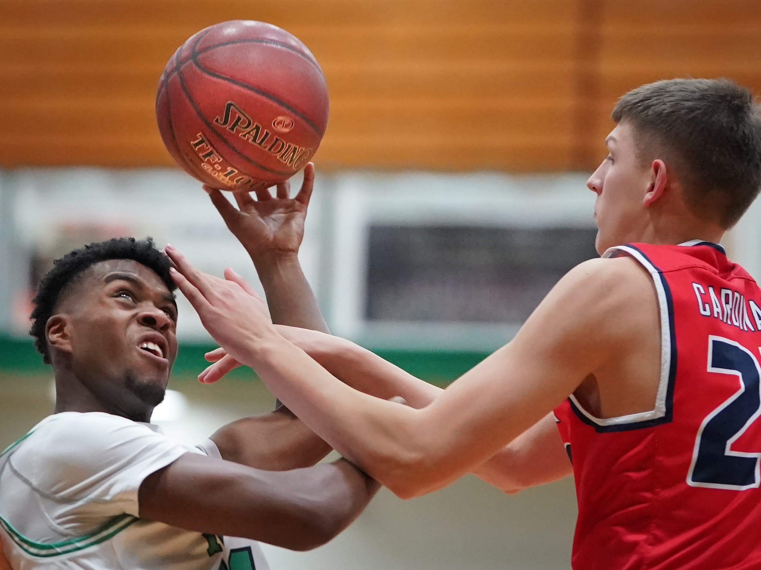 Abe Schiek (11) of Oshkosh North tries to get a shot past Elliot Parks (22) of Pacelli. The Oshkosh North Spartans hosted the Stevens Point Pacelli Catholic Cardinals in the Friday night game of the Fox River Brewing Thanksgiving Classic Tournament.
