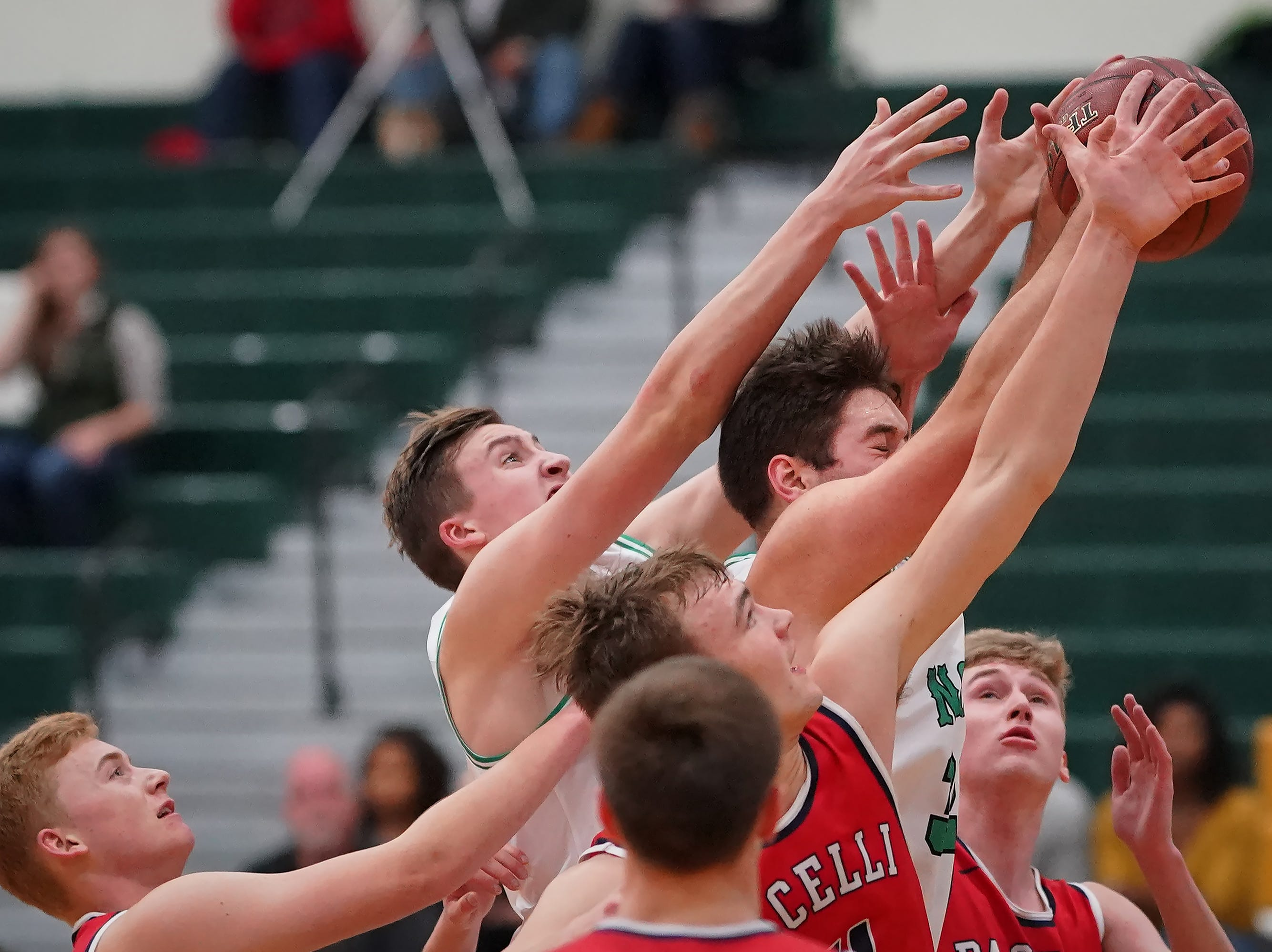 Matt Hickey (32) of Oshkosh North battles for a rebound. The Oshkosh North Spartans hosted the Stevens Point Pacelli Catholic Cardinals in the Friday night game of the Fox River Brewing Thanksgiving Classic Tournament.