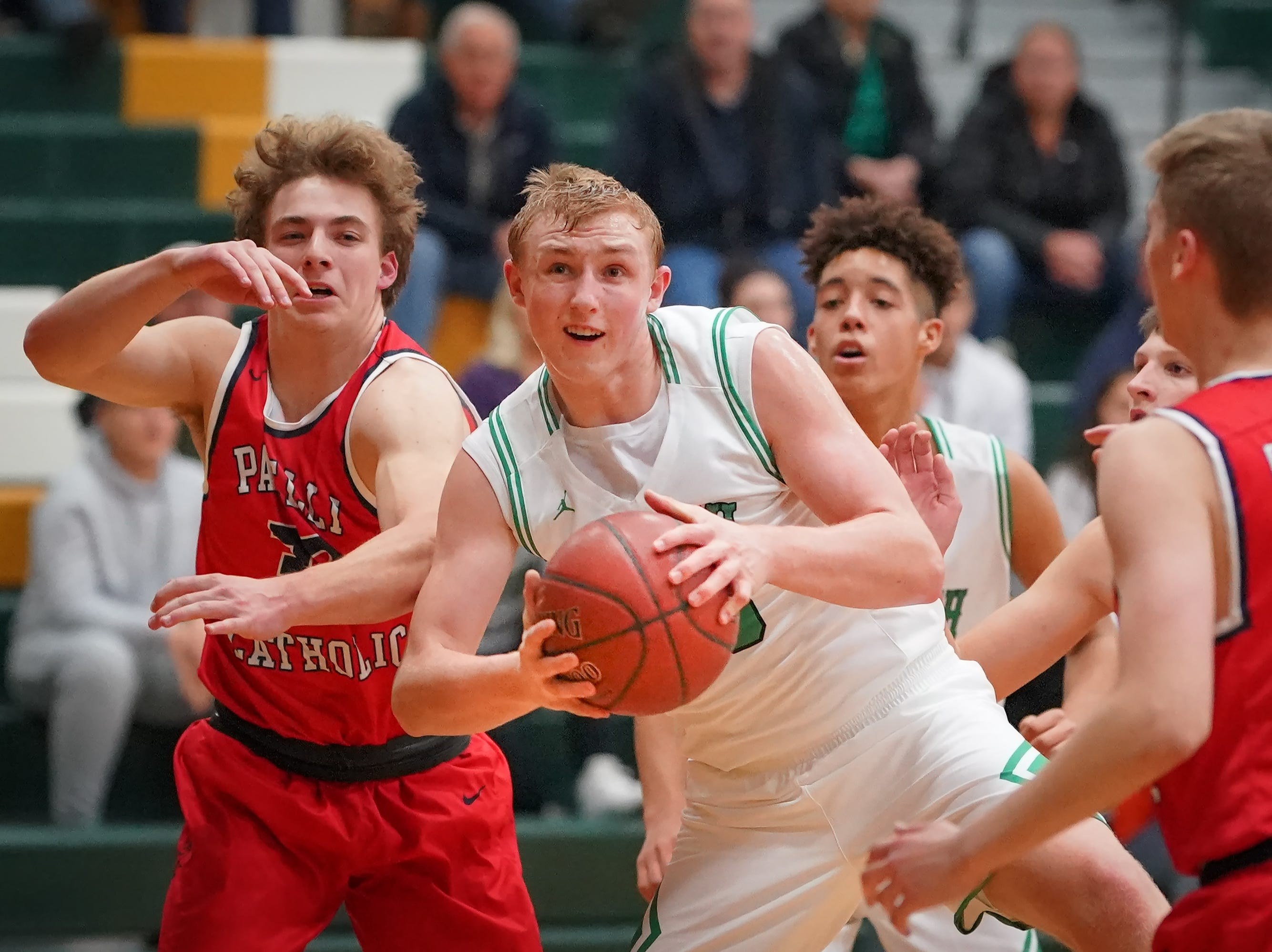 Matthew Berger (30) of Oshkosh North tries to move the ball past Nick Hartman (24) of Pacelli. The Oshkosh North Spartans hosted the Stevens Point Pacelli Catholic Cardinals in the Friday night game of the Fox River Brewing Thanksgiving Classic Tournament.