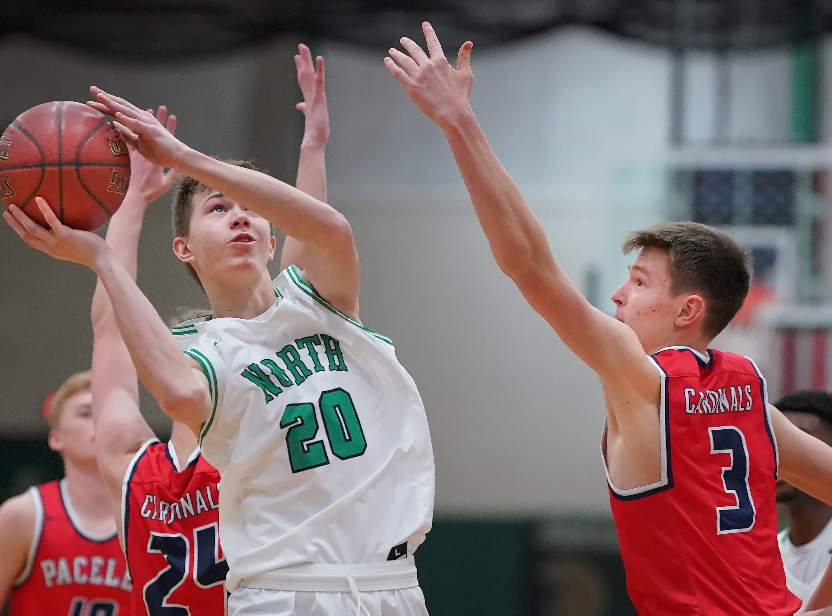 Brennon Colburn (20) of Oshkosh North fights for a shot. The Oshkosh North Spartans hosted the Stevens Point Pacelli Catholic Cardinals in the Friday night game of the Fox River Brewing Thanksgiving Classic Tournament.