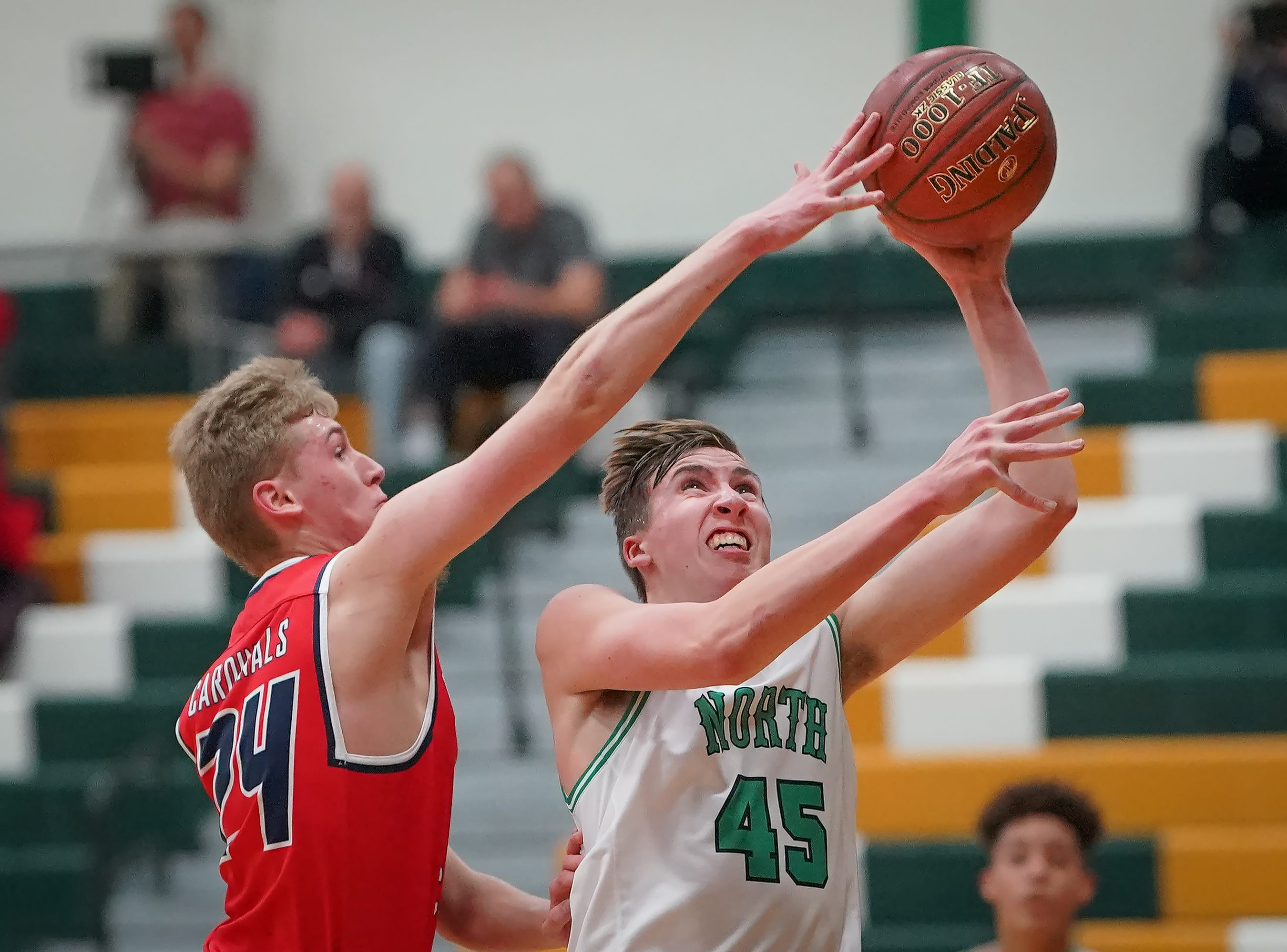 Luke Salzsieder (45) of Oshkosh North gets a shot off while guarded by Nick Hartman (24) of Pacelli. The Oshkosh North Spartans hosted the Stevens Point Pacelli Catholic Cardinals in the Friday night game of the Fox River Brewing Thanksgiving Classic Tournament.