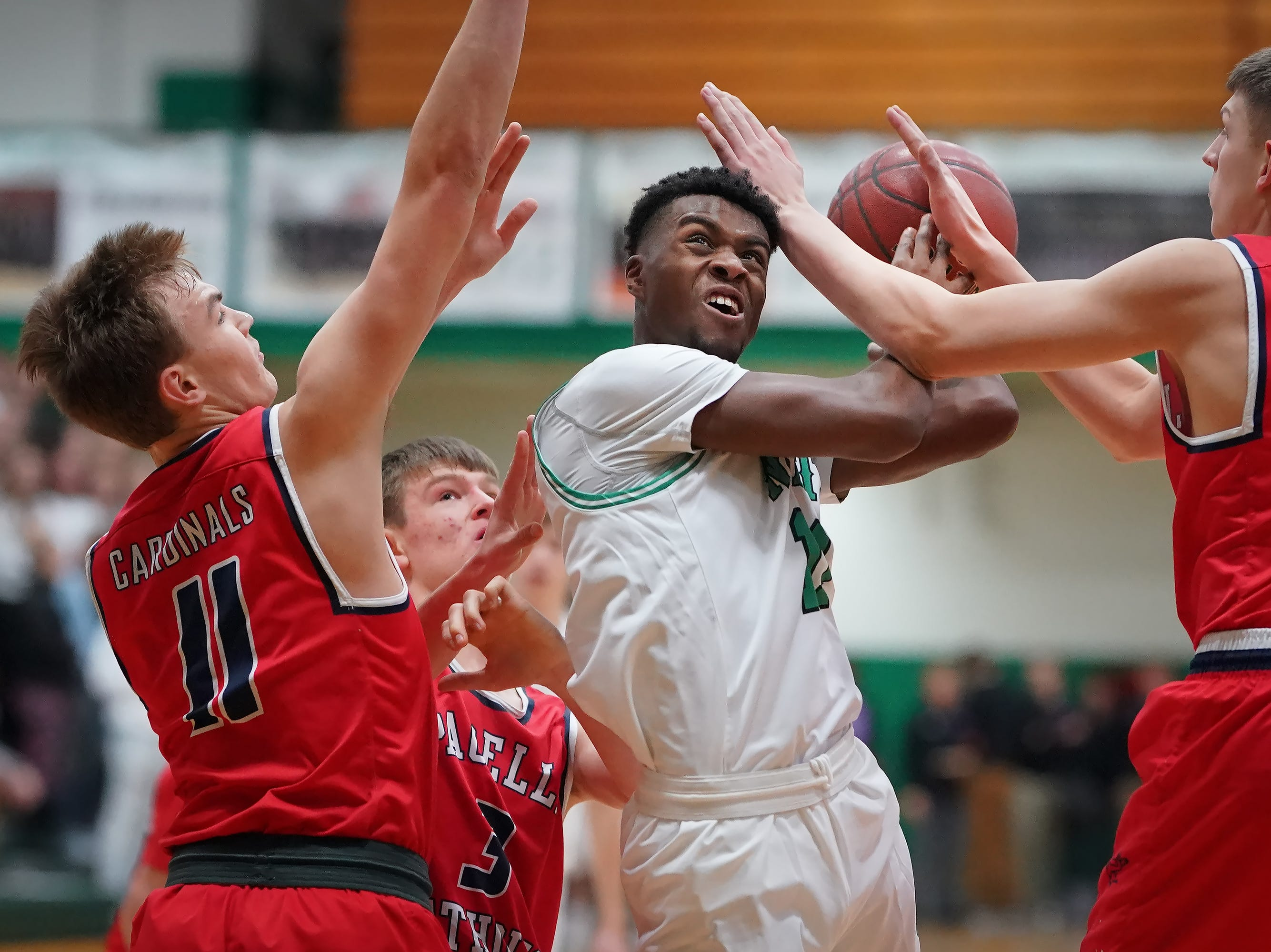 Abe Schiek (11) of Oshkosh North battles his way to the basket. The Oshkosh North Spartans hosted the Stevens Point Pacelli Catholic Cardinals in the Friday night game of the Fox River Brewing Thanksgiving Classic Tournament.