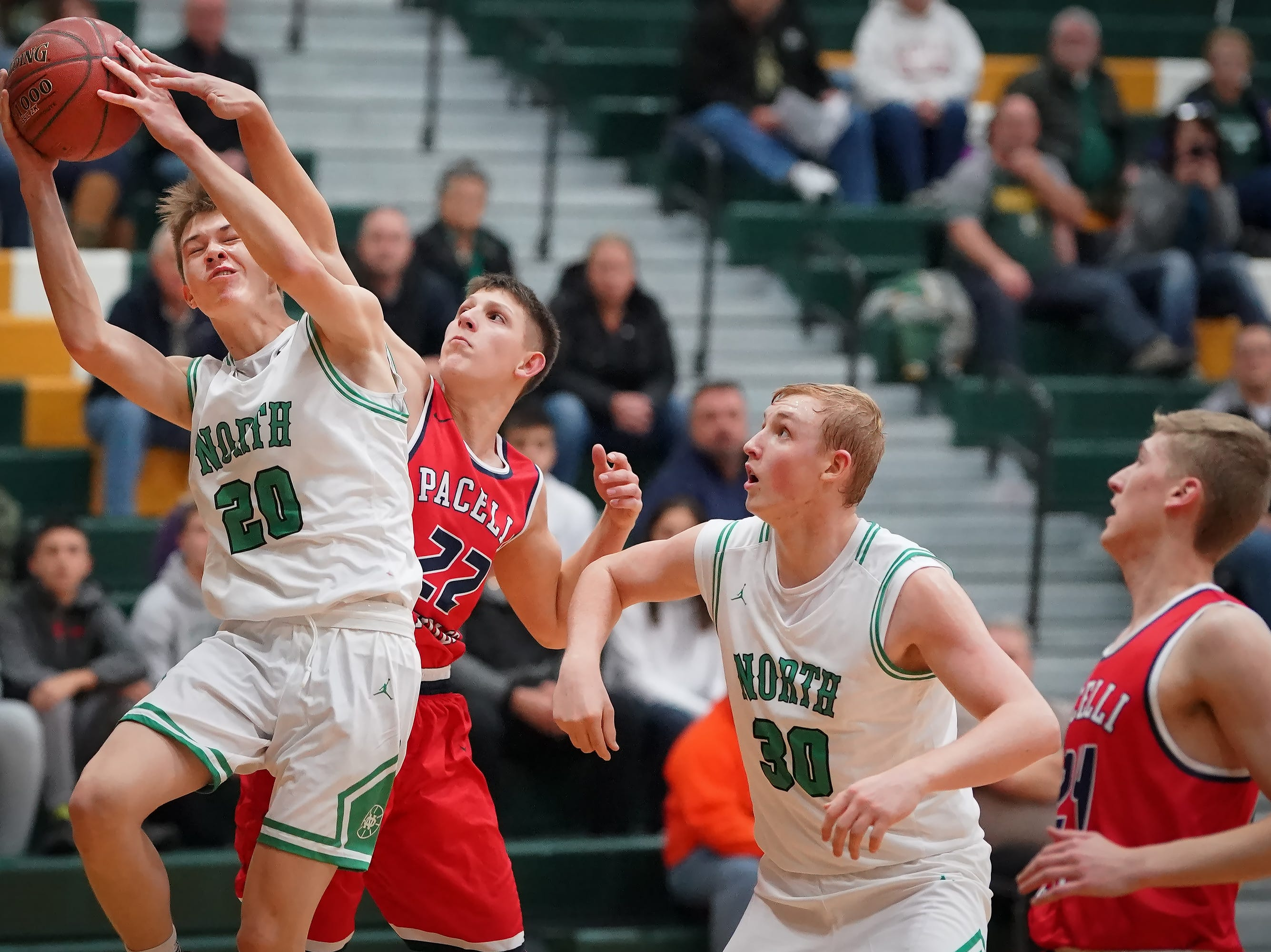 Brennon Colburn (20) of Oshkosh North pulls a rebound away from Elliot Parks (22) of Pacelli. The Oshkosh North Spartans hosted the Stevens Point Pacelli Catholic Cardinals in the Friday night game of the Fox River Brewing Thanksgiving Classic Tournament.