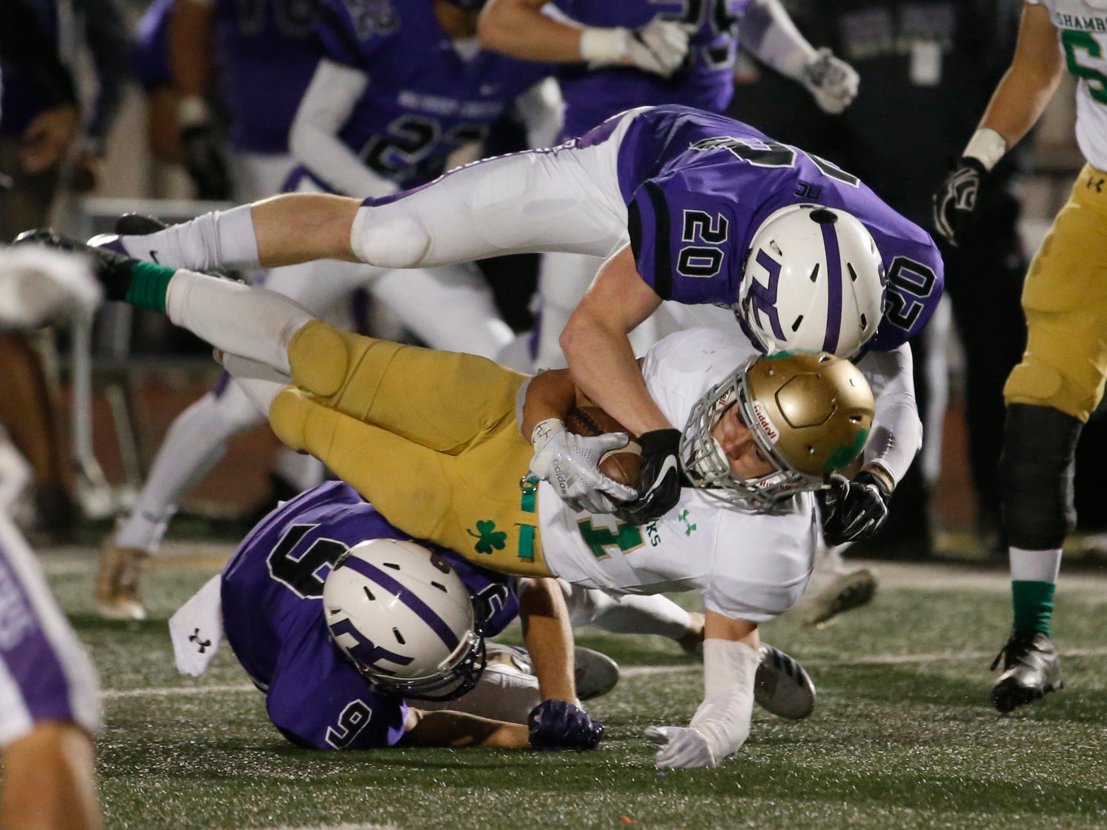 Northwest Christian's Brady Wijbrandts (9) and Josh Heidel (20) tackle Puma Catholic's Ean Chavez (21) during the 3A state championship game Nov. 24 at Campo Verde High School.