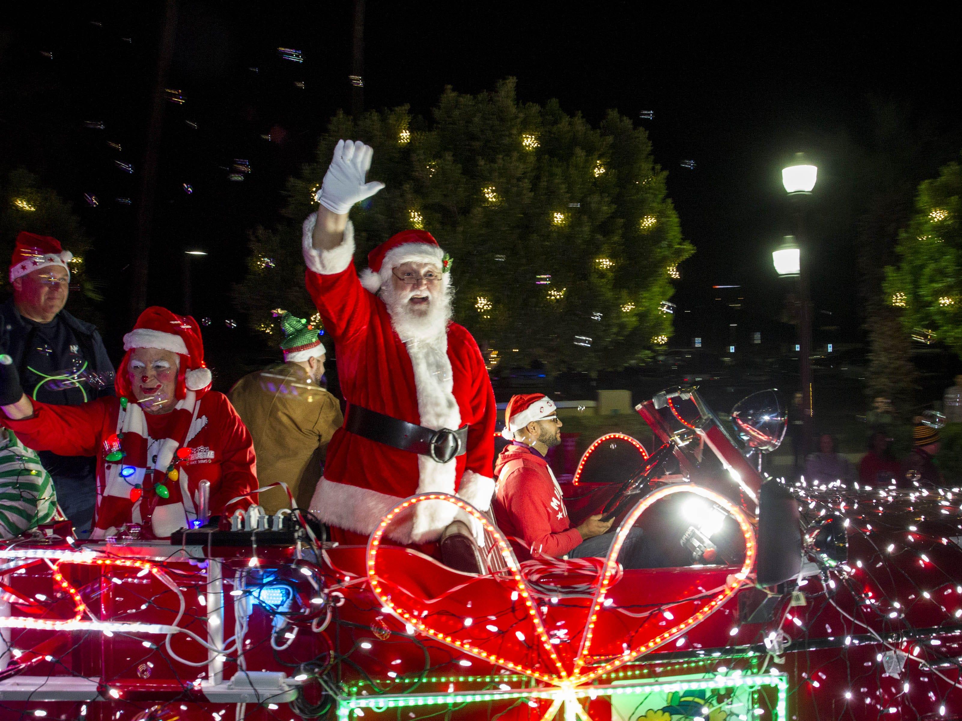 Santa Claus waves to kids along Mill Avenue during the 2018 Fantasy of Lights Parade, Friday Nov. 23, 2018.