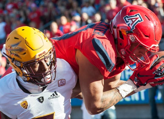Nov 24, 2018; Tucson, AZ, USA; Arizona Wildcats wide receiver Shawn Poindexter (19) catches the ball for a touchdown against Arizona State Sun Devils defensive back Kobe Williams (left) during the first half of the Territorial Cup at Arizona Stadium. Mandatory Credit: Casey Sapio-USA TODAY Sports