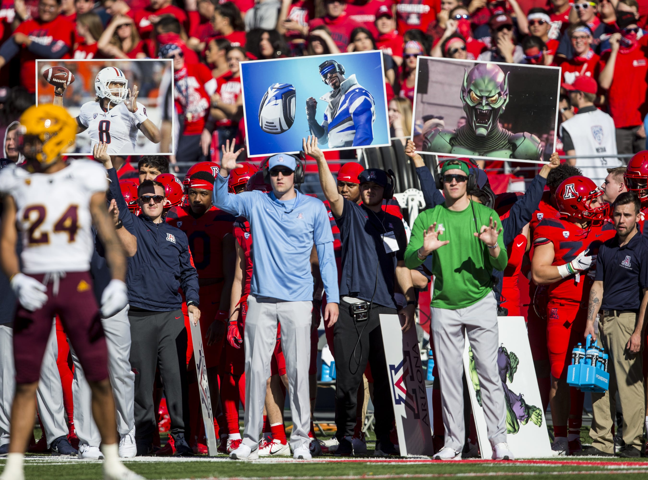 Arizona personnel hold up play signals during the first half of the Territorial Cup on Saturday, Nov. 24, 2018, at Arizona Stadium in Tucson, Ariz.