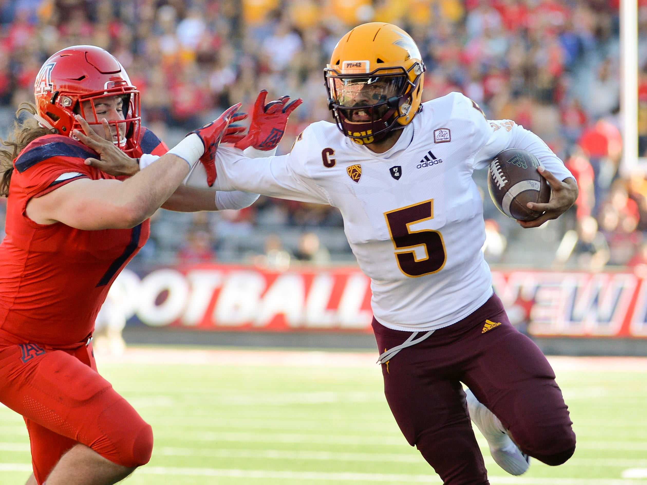 Nov 24, 2018; Tucson, AZ, USA; Arizona State Sun Devils quarterback Manny Wilkins (5) runs the ball against Arizona Wildcats linebacker Colin Schooler (7) during the first half of the Territorial Cup at Arizona Stadium. Mandatory Credit: Casey Sapio-USA TODAY Sports