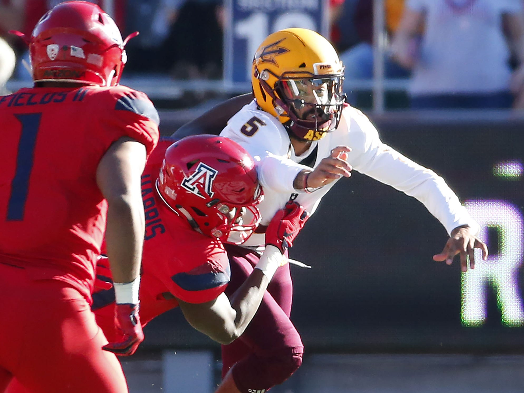 Arizona Wildcats defensive end Jalen Harris (49) causes Arizona State Sun Devils quarterback Manny Wilkins (5) to fumble the ball during the Territorial Cup football game at Arizona Stadium in Tucson on November 24.