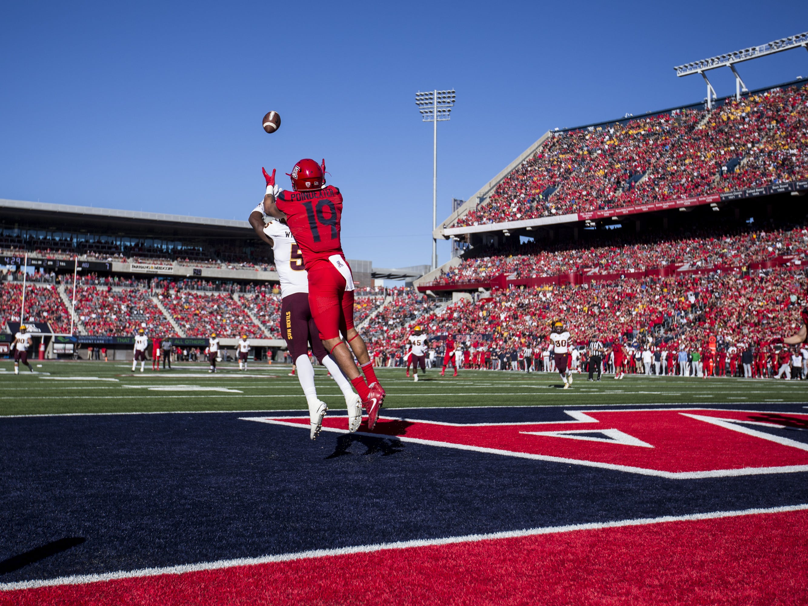 Arizona's Shawn Poindexter scores a touchdown reception over Arizona State's Kobe Williams during the first half of the Territorial Cup on Saturday, Nov. 24, 2018, at Arizona Stadium in Tucson, Ariz.