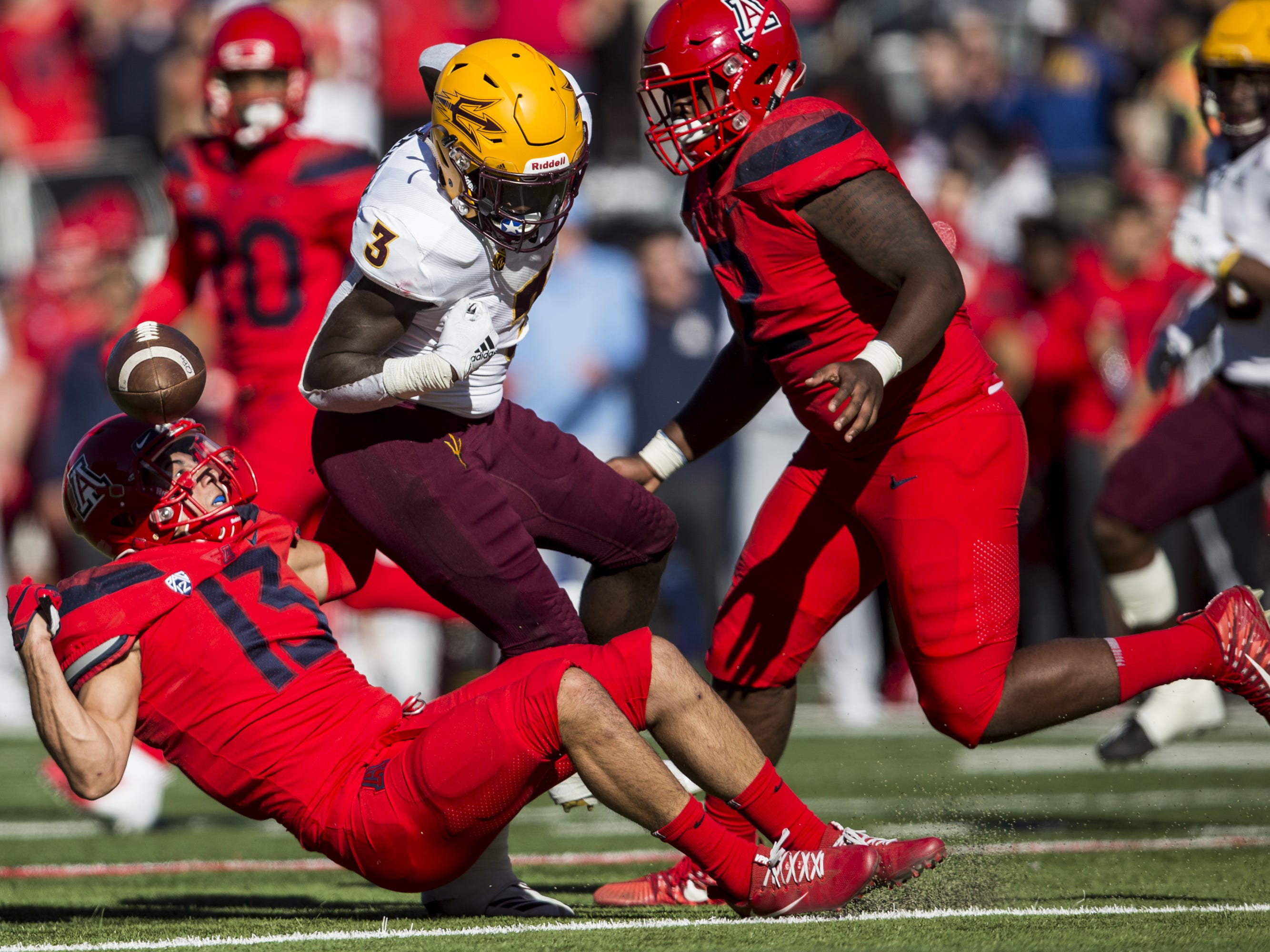 Arizona's Chacho Ulloa (13) strips the ball from Arizona State's Eno Benjamin during the first half of the Territorial Cup on Saturday, Nov. 24, 2018, at Arizona Stadium in Tucson, Ariz.