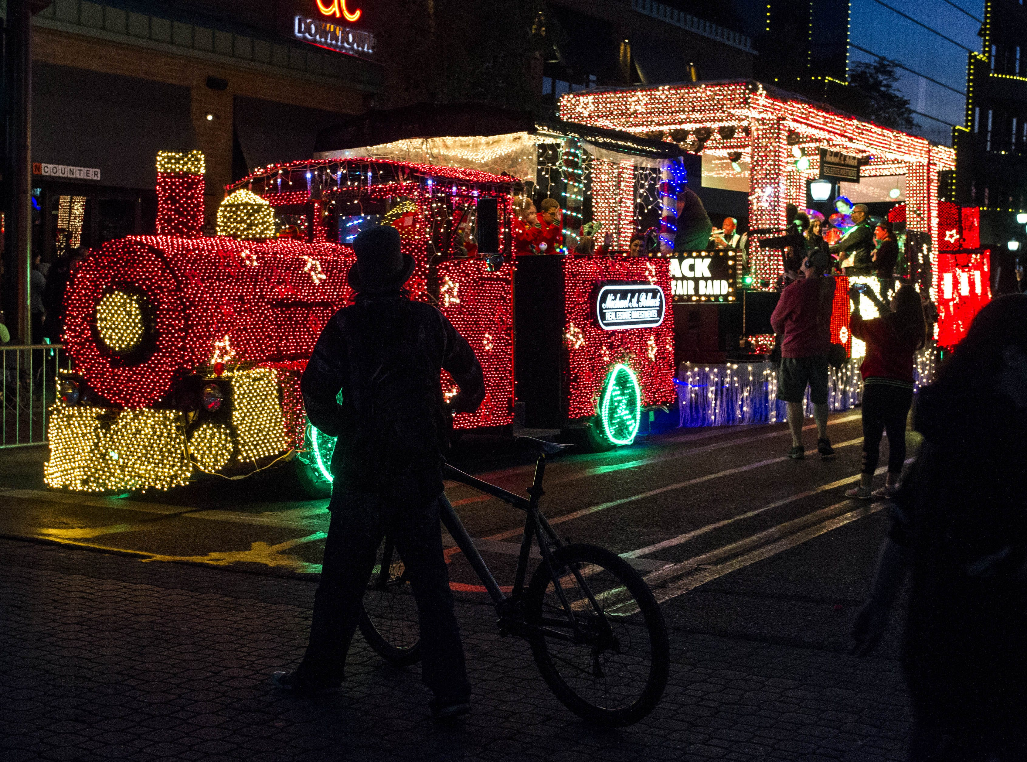 Onlookers check out Michael A. Pollack's train float during the 2018 Fantasy of Lights Parade on Mill Ave. in downtown Tempe Friday, Nov. 23, 2018.