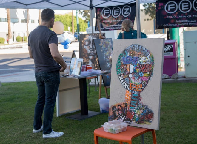 Artists performed outside of small businesses as part of 850zip and American Express' Small Business Saturday. Aaron Allen Marner worked on a painting outside of FEZ.