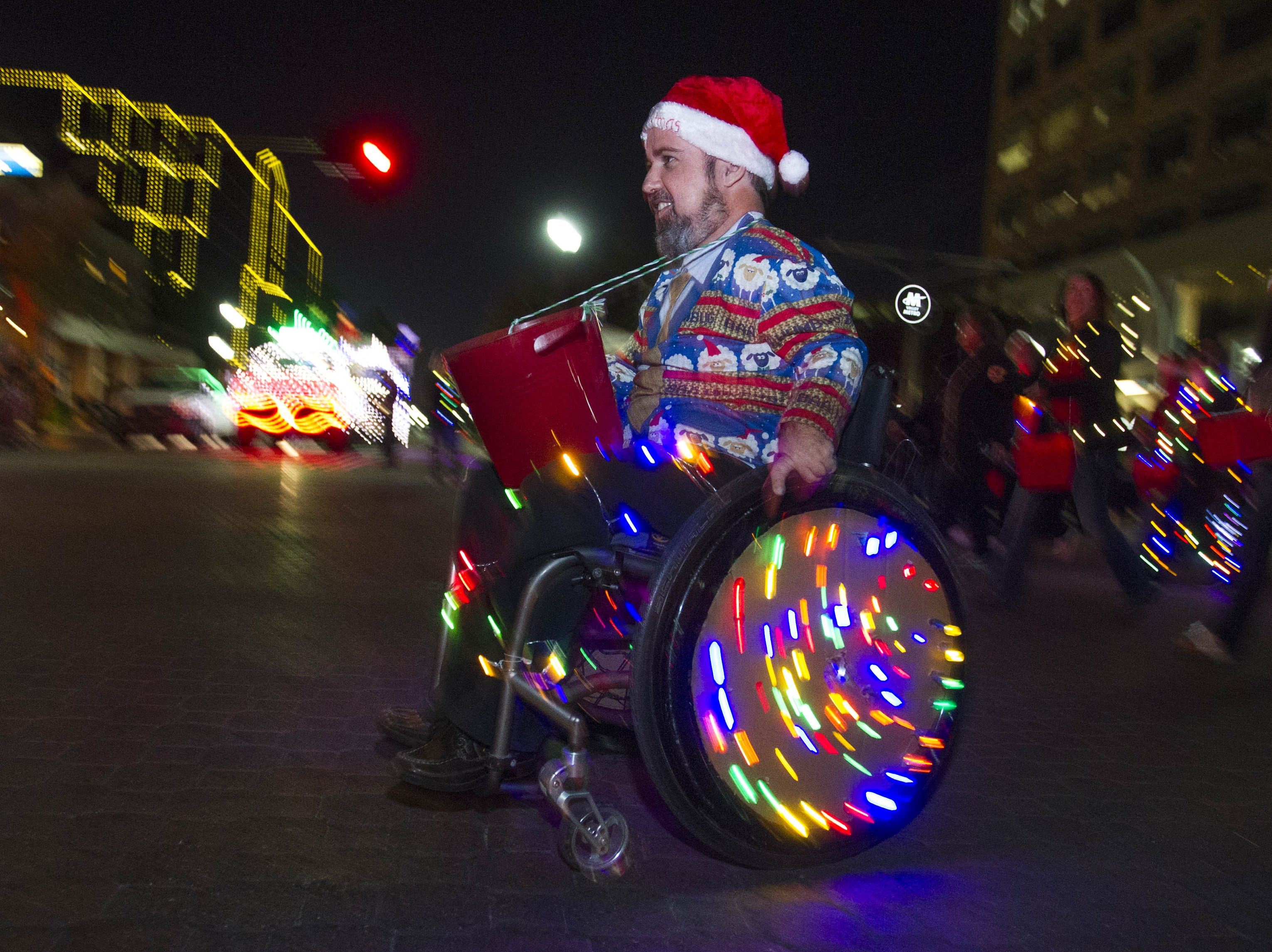 A Light Parade participate throws out out candy to the crowd during the 2018 Fantasy of Lights Parade on Mill Ave. Friday, Nov. 23, 2018.