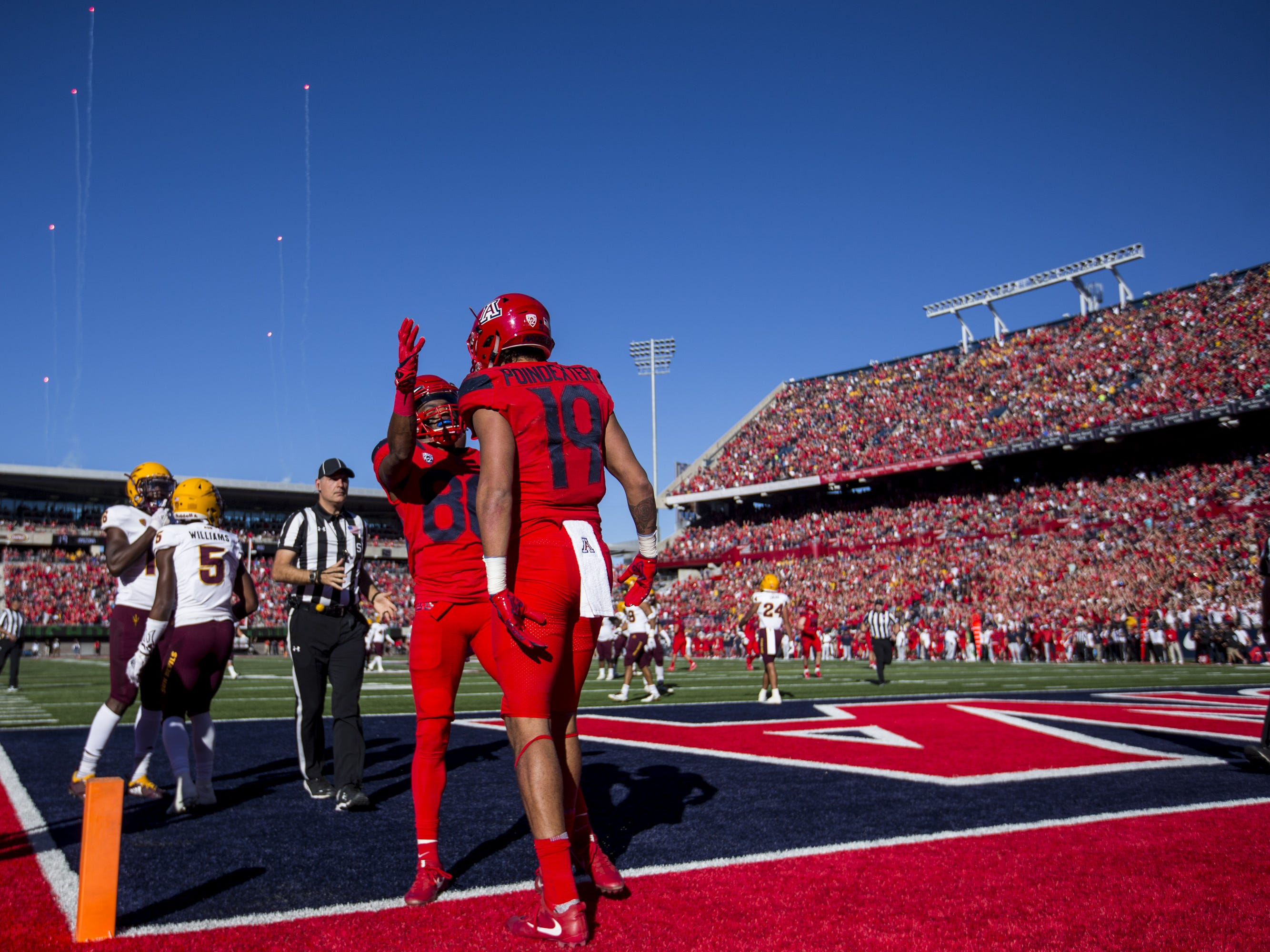 Arizona's Shawn Poindexter (19) celebrates with Stanley Berryhill III after Poindexter scored a touchdown reception against Arizona State during the first half of the Territorial Cup on Saturday, Nov. 24, 2018, at Arizona Stadium in Tucson, Ariz.