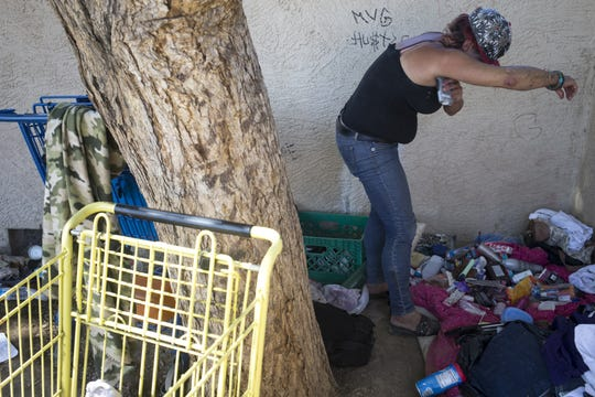 Jenna Ware puts on deodorant, June 27, 2018, in the alley she lives in behind Bonsall Park, 59th Avenue and Bethany Home Roads, Glendale.
