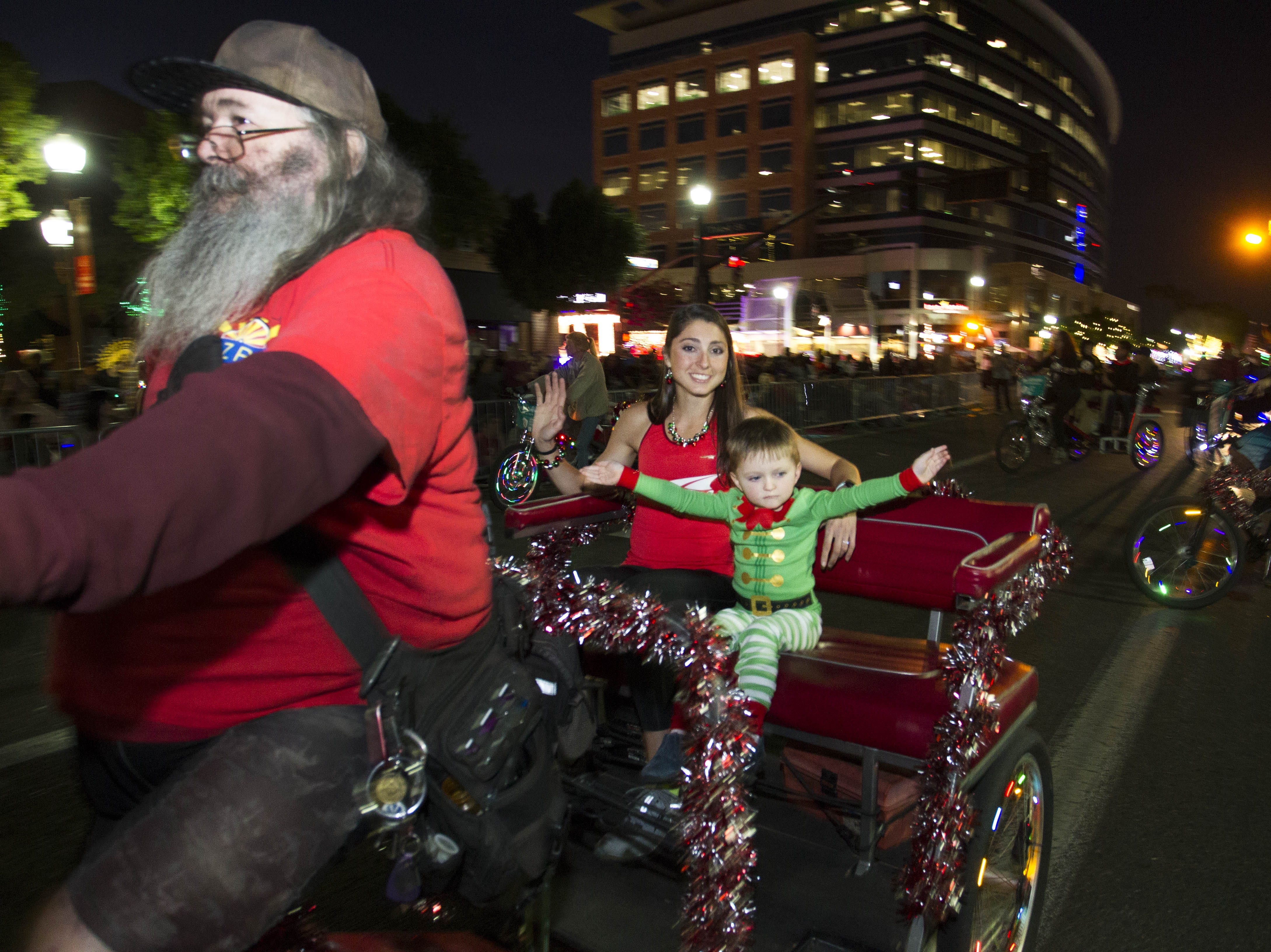 Grand Marshall Sarah Sellers and her nephew Dallin Callister 4, start off the 2018 Fantasy of Lights parade on Mill Ave. in downtown Tempe Friday, Nov. 23, 2018.