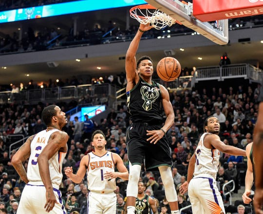 Bucks forward Giannis Antetokounmpo dunks the ball in front of a crowd of Suns players during the second quarter of a game on Nov. 23 in Milwaukee.