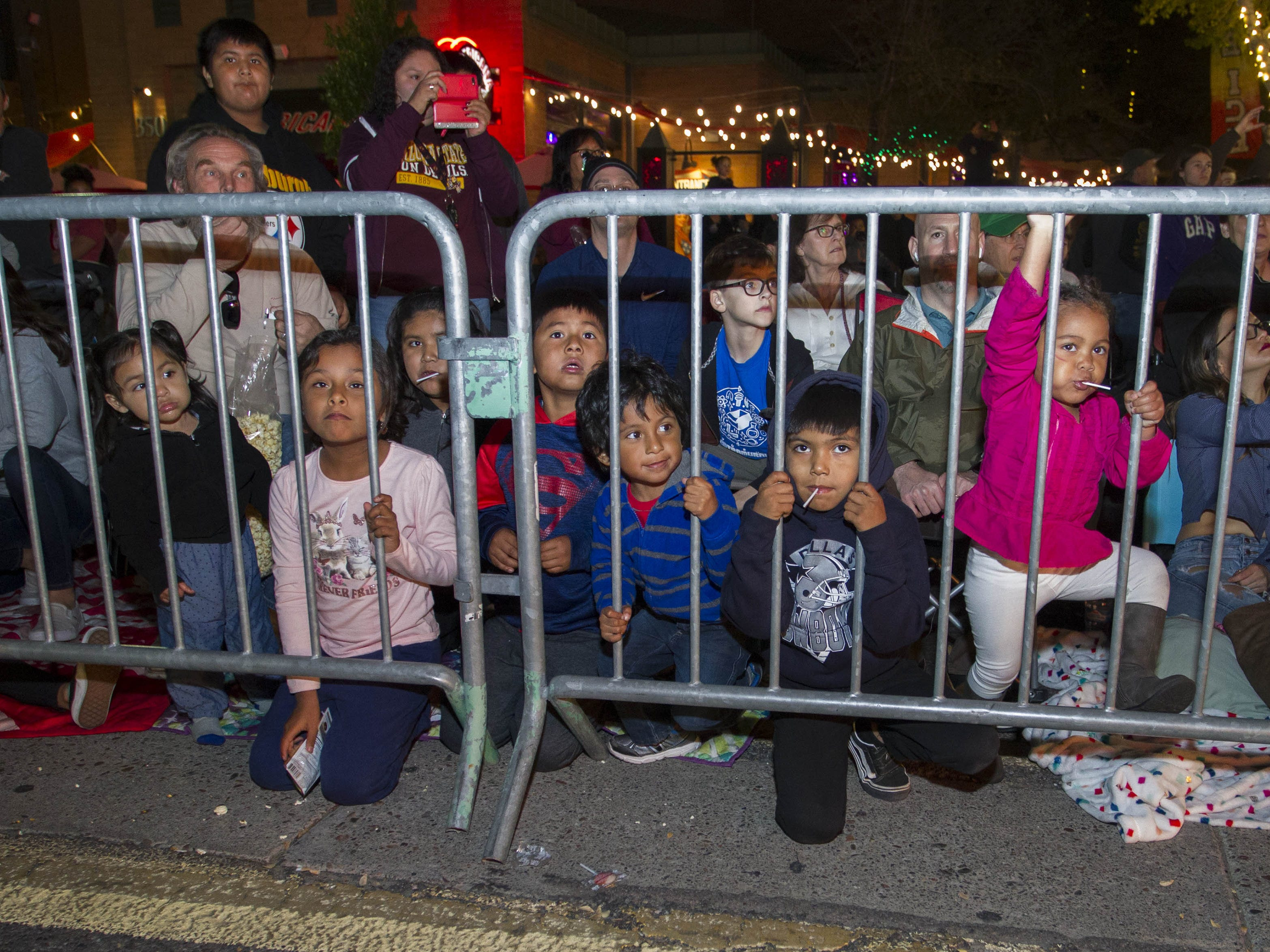 Kids watch with fascination as floats make their way down Mill Ave. during the 2018 Fantasy of Lights Parade in downtown Tempe Friday, Nov. 23, 2018.