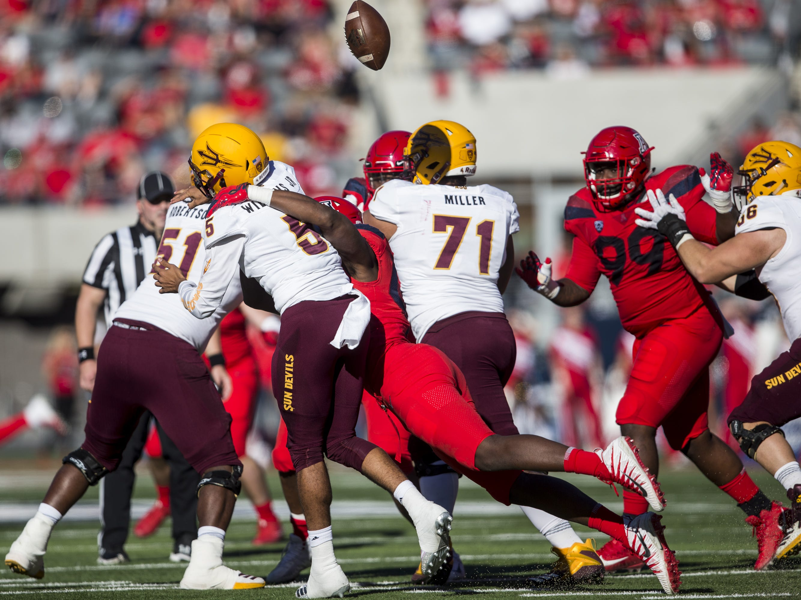 Arizona State's Manny Wilkins fumbles the ball after being hit by Arizona's Jalen Harris during the first half of the Territorial Cup on Saturday, Nov. 24, 2018, at Arizona Stadium in Tucson, Ariz.