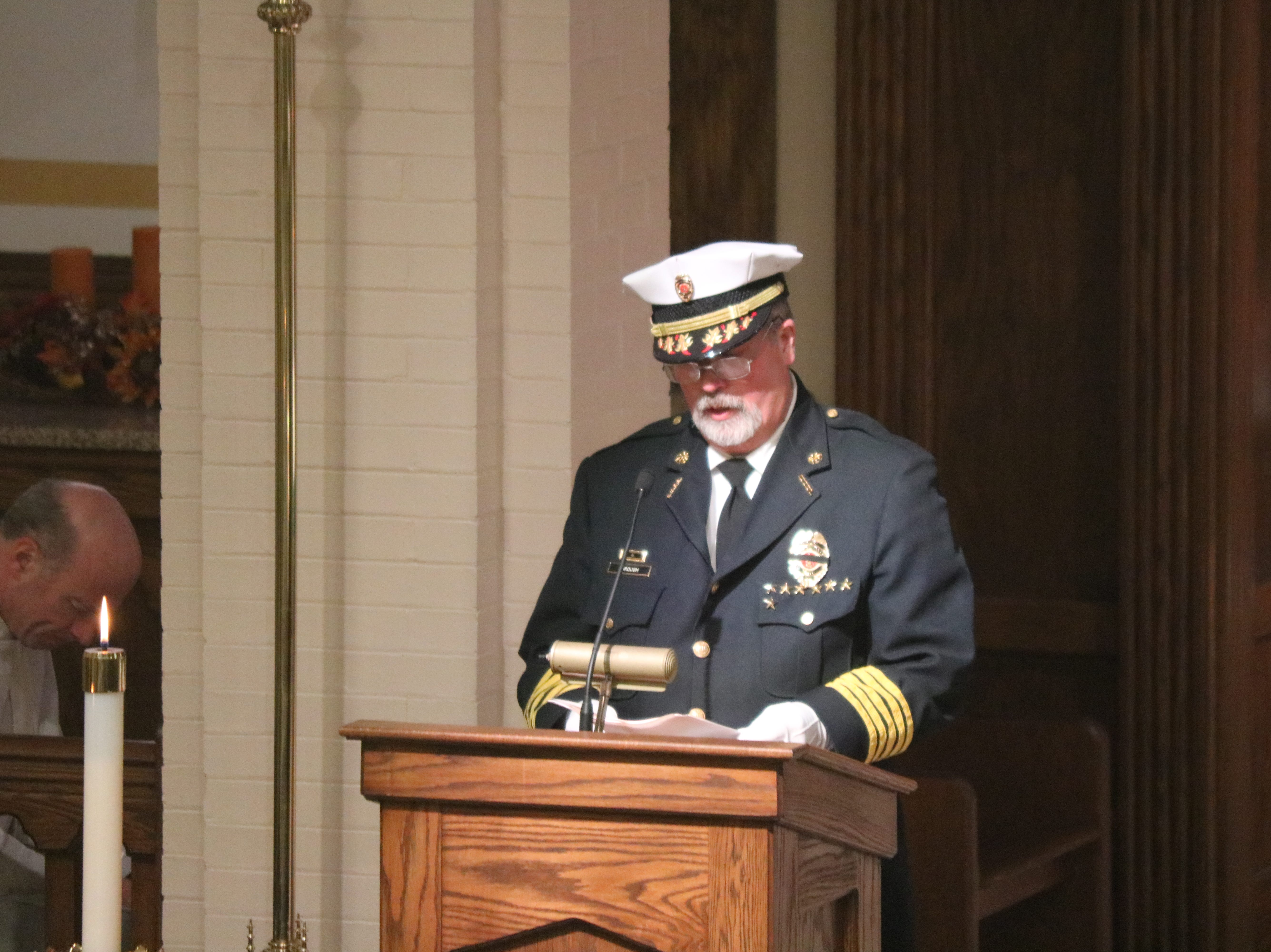 Carroll Township Fire Chief John Brough speaks at the funeral of firefighter Daniel Lucius in Oak Harbor on Saturday.