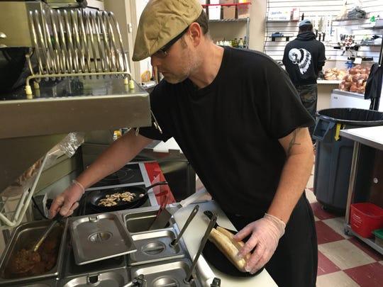Jason Malone prepares a meatball sub at Moe's Corner Deli during Small Business Saturday in Port Huron.