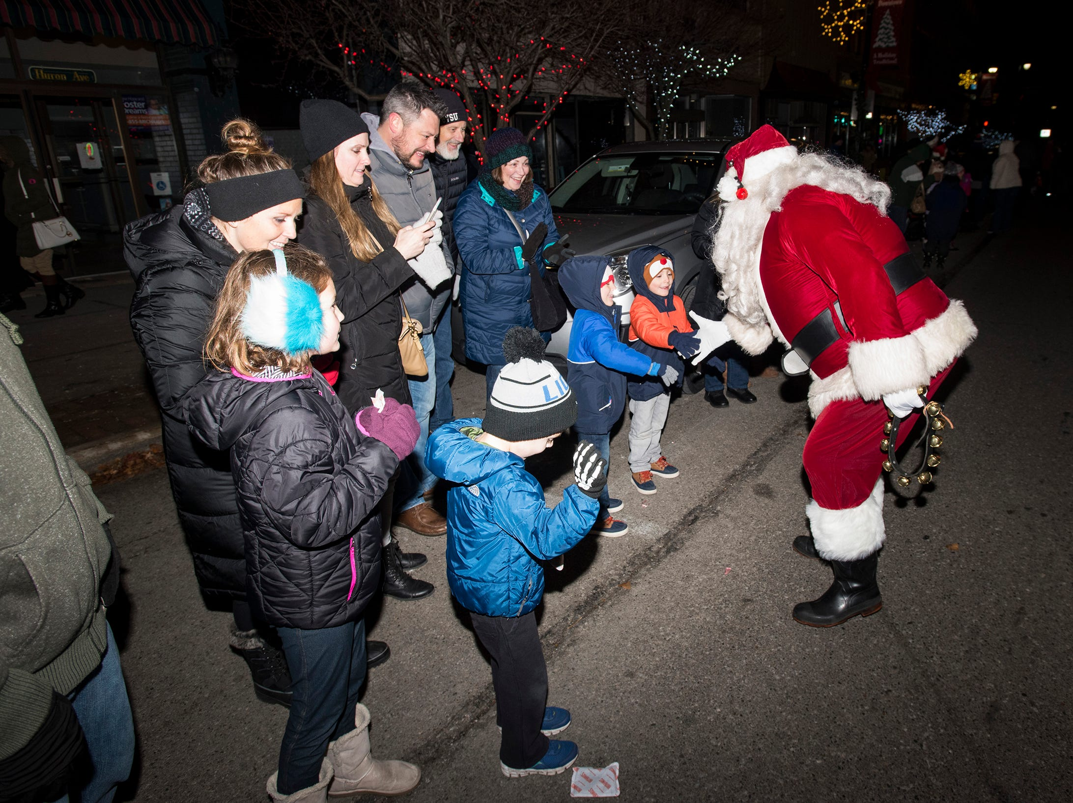 Santa Claus stops to talk to a group of kids during Sperry's Santa Claus Parade Friday, Nov. 23, 2018 in downtown Port Huron.